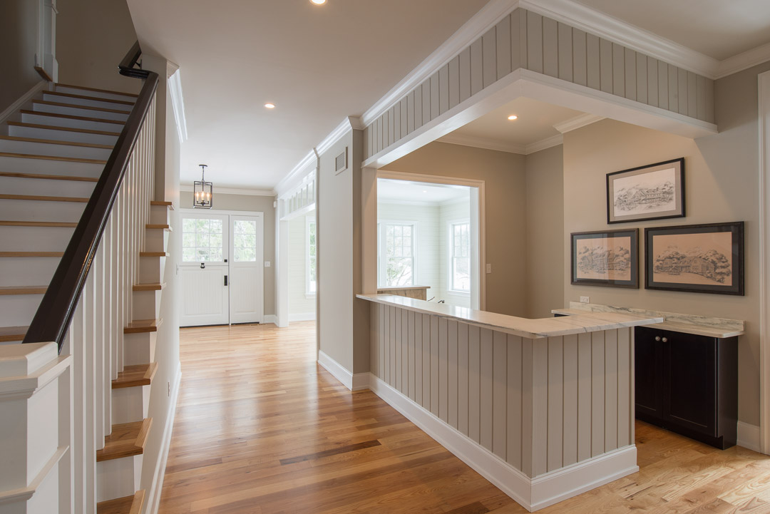 Berwyn Nantucket custom home foyer with staircase and custom bar