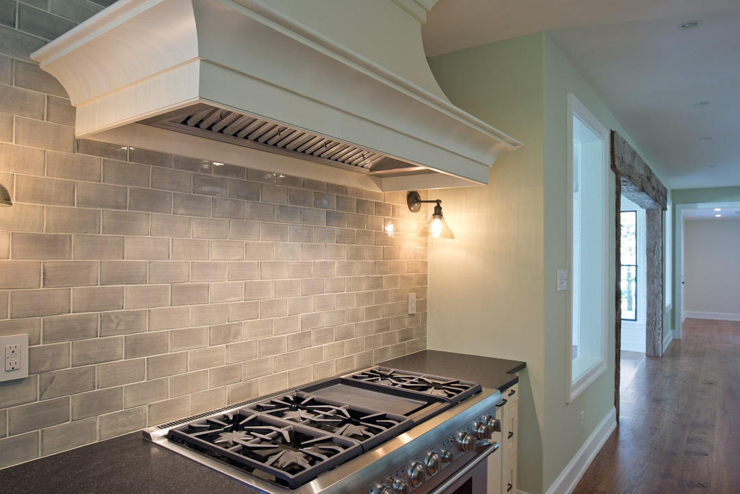 Winslow Interiors - built-in range with hood and subway tile
